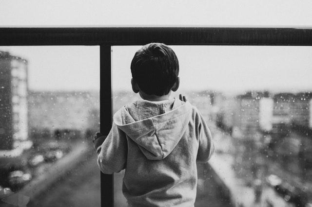 Malý chlapček otočený tvárou k sklenenému zábradliu.jpg