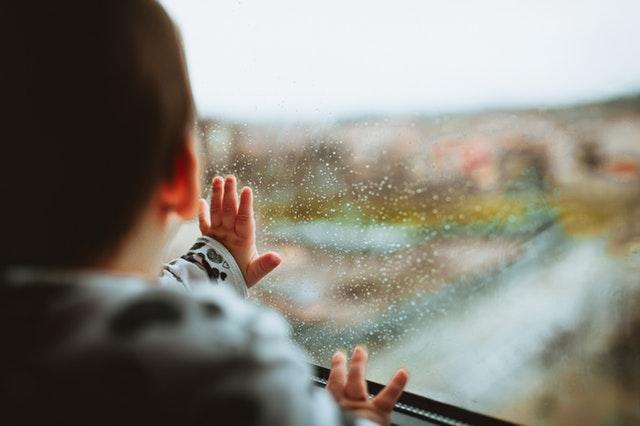 Malé dieťa chytá rukami sklenenú tabuľu.jpg