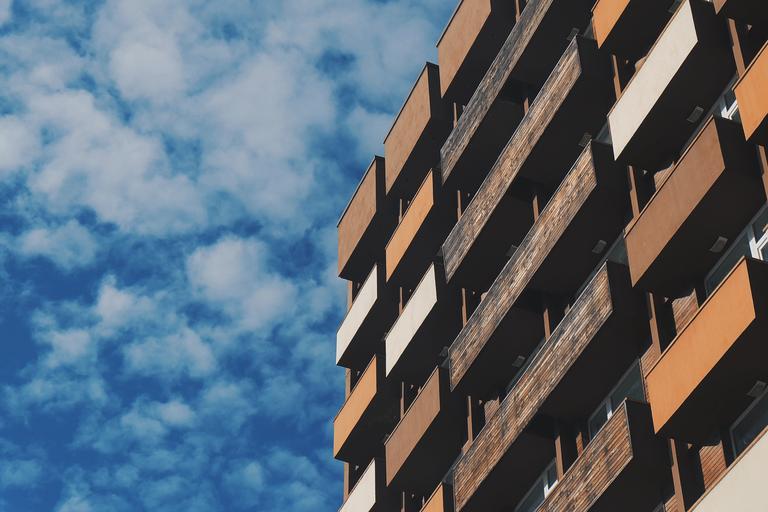 Moderný panelák s drevenými modernými zábradliami na balkónoch.jpg