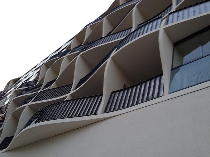 Panelák s oblými balkónmi, na ktorých sú sklenené a kovové zábradlia.jpg